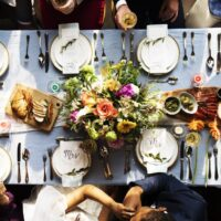 Groom kissing bride hand in wedding reception aerial view